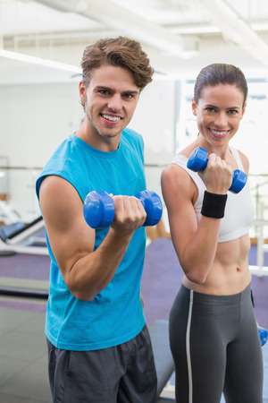 Fit couple exercising together with blue dumbbells at the gym photo