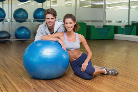 Fit woman leaning on exercise ball with trainer smiling at camera at the gym photo