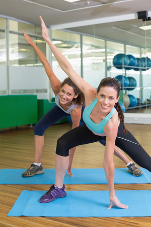 fit women: Fit women stretching on exercise mats  at the gym Stock Photo