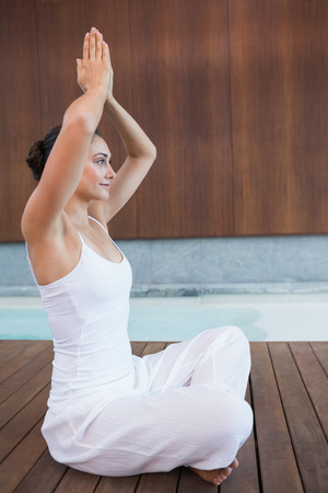 Content brunette in white sitting in lotus pose with hands together in health spa photo