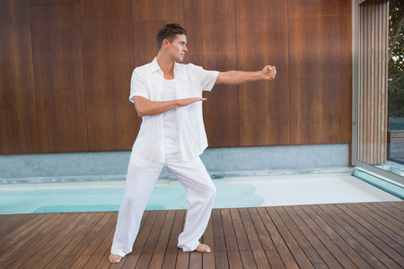 tai chi: Handsome man in white doing tai chi in health spa