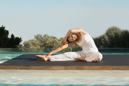 janu: Peaceful brunette in janu sirsasana yoga pose poolside on a sunny day at the spa