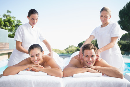 massage table: Smiling couple enjoying couples massage poolside outside at the spa