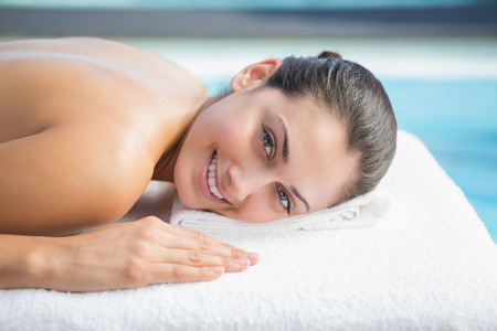 Smiling brunette lying on massage table poolside outside at the spa photo