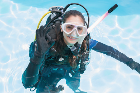 Smiling woman on scuba training in swimming pool making ok sign on a sunny day photo