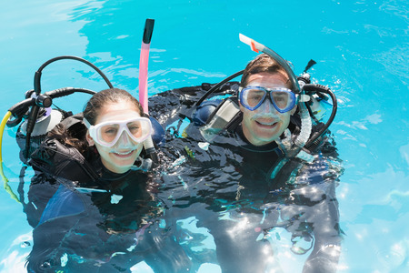 scuba woman: Smiling couple on scuba training in swimming pool looking at camera on a sunny day Stock Photo