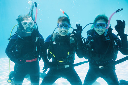 scuba woman: Friends on scuba training submerged in swimming pool making ok sign on their holidays