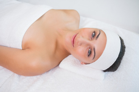 smiing: Peaceful smiing brunette lying on massage table in the health spa
