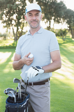 Handsome golfer standing with golf bag on a sunny day at the golf course photo