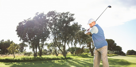 Golfer swinging on the grass on a sunny day at the golf course photo