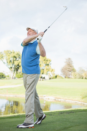 Golfer taking a shot and smiling on a sunny day at the golf course photo