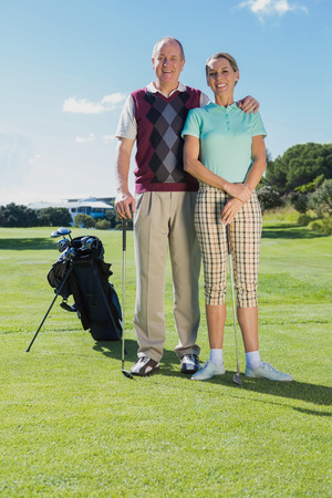 Golfing couple standing smiling at camera on a sunny day at the golf course photo