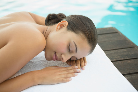 Peaceful brunette lying on towel poolside outside at the spa photo