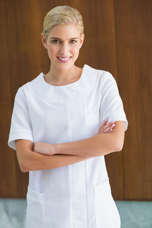 Blonde beauty therapist smiling at camera at the spa