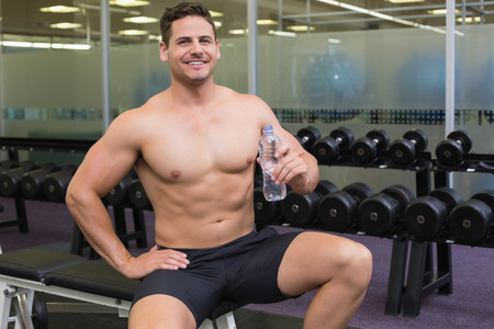 Shirtless bodybuilder sitting on bench with water bottle at the gym photo