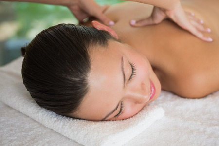 therapy room: Brunette enjoying a peaceful massage with eyes closed at the health spa