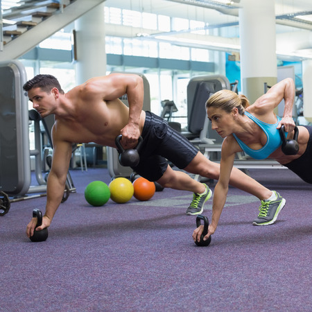 plank position: Bodybuilding man and woman lifting kettlebells in plank position at the gym Stock Photo