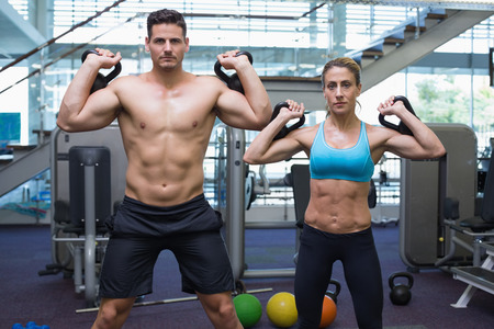 Bodybuilding man and woman lifting kettlebells looking at camera at the gym photo