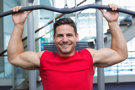 weight machine: Handsome smiling bodybuilder using weight machine for arms at the gym
