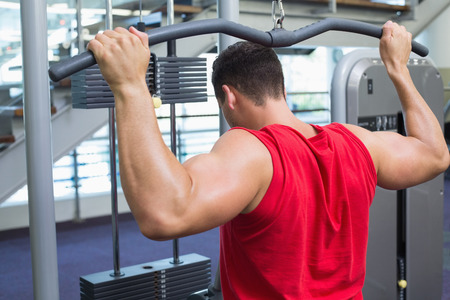 weight machine: Strong bodybuilder using weight machine for arms at the gym Stock Photo