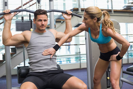 weight machine: Bodybuilder using weight machine for arms with encouraging trainer at the gym Stock Photo