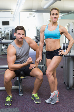 Bodybuilding man and woman posing for the camera at the gym photo