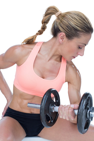 Strong woman doing bicep curl with large dumbbell on white background photo