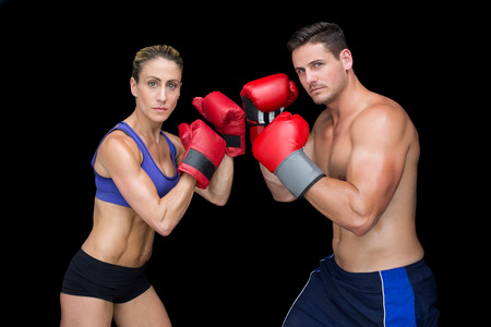 lean out: Bodybuilding couple posing with boxing gloves looking at camera on black background