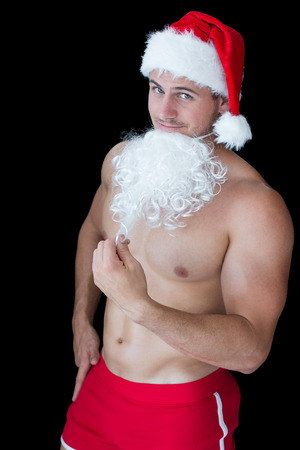 Smiling muscular man posing in sexy santa outfit with fake beard on black background