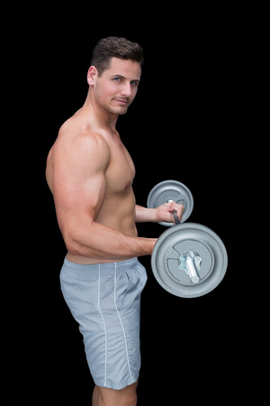 Happy handsome crossfitter lifting up barbell on black background photo