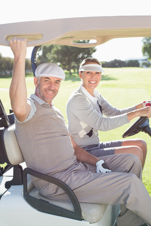 Happy golfing couple smiling at camera in their buggy on a sunny day at the golf course photo