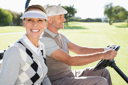Happy golfing couple driving in their buggy on a sunny day at the golf course photo
