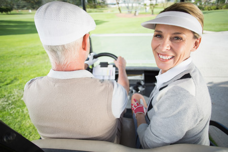Golfing couple driving in their golf buggy with woman smiling at camera on a sunny day at the golf course photo
