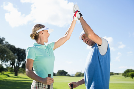 Golfing couple high fiving on the golf course on a sunny day at the golf course photo