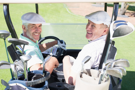 Golfing friends driving in their golf buggy smiling at camera on a sunny day at the golf course photo