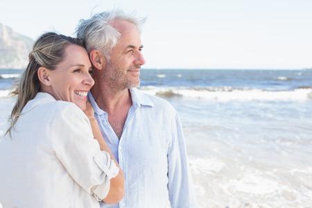 Gelukkig paar knuffelen op het strand kijkt uit op zee op een zonnige dag