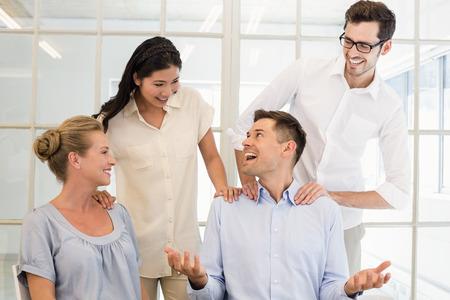 congratulating: Casual business team congratulating colleague in the office