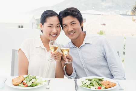 Happy asian couple having meal together at home on the balcony photo