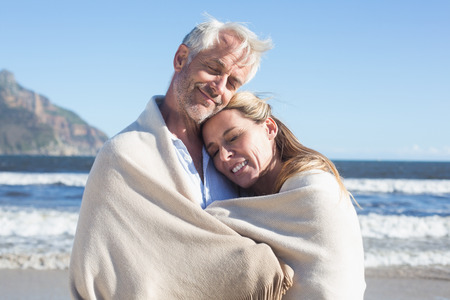 wrapped up: Smiling couple wrapped up in blanket on the beach on a sunny day