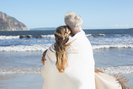 wrapped up: Couple wrapped up in blanket on the beach looking out to sea on a sunny day