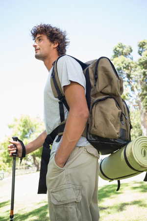 walking pole: Handsome hiker holding walking pole on a sunny day