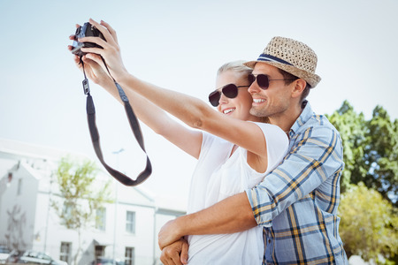 Stylish young couple taking a selfie on a sunny day in the city photo