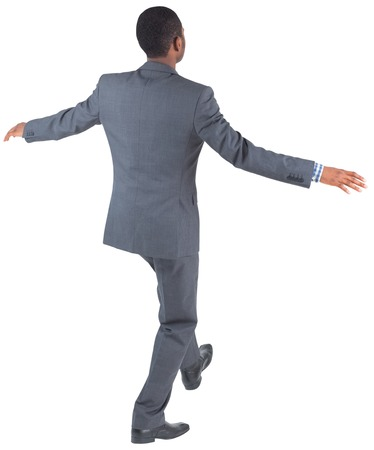 Businessman performing a balancing act on white background photo