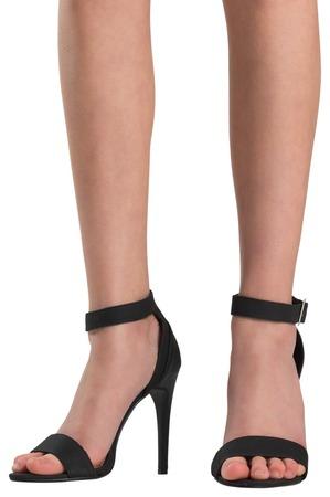 heel strap: Female feet in black sandals on white background