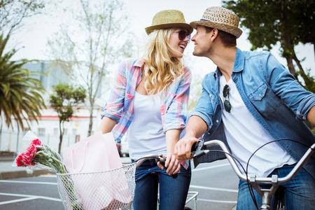 parejas de amor: Pareja joven de la cadera en un paseo en bicicleta en un d�a soleado en la ciudad