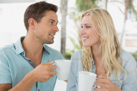 Hip young couple having coffee together on the cafe terrace on sunny day photo