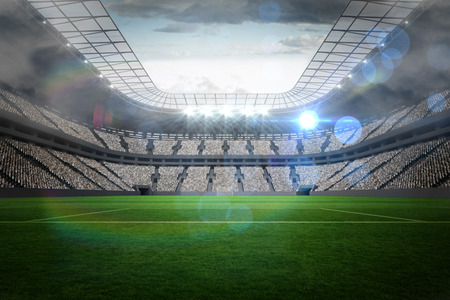 soccer pitch: Large football stadium with lights under cloudy sky