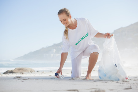 activist: Blonde activist picking up trash on the beach on a sunny day