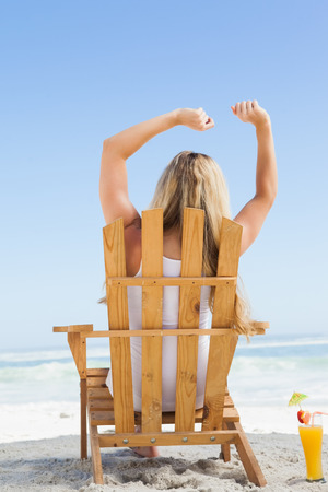 Pretty blonde sitting in deck chair with a cocktail on a sunny day photo