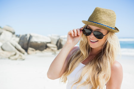 Stylish blonde smiling at camera on the beach on a sunny day photo